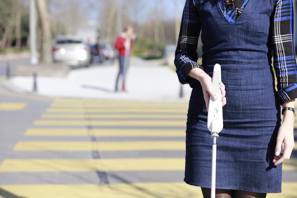 A WeWALKer using WeWALK while crossing the street