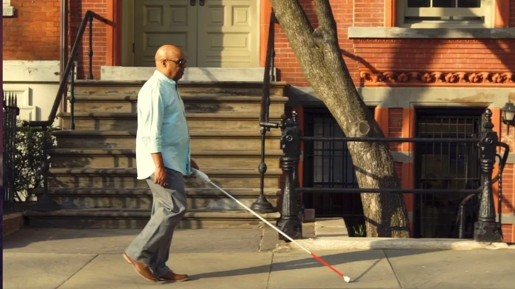 Man is walking with WeWALK down the street