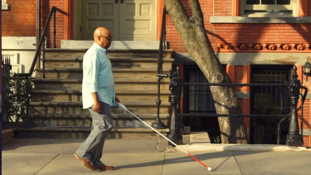 Man is walking with WeWALK down the street