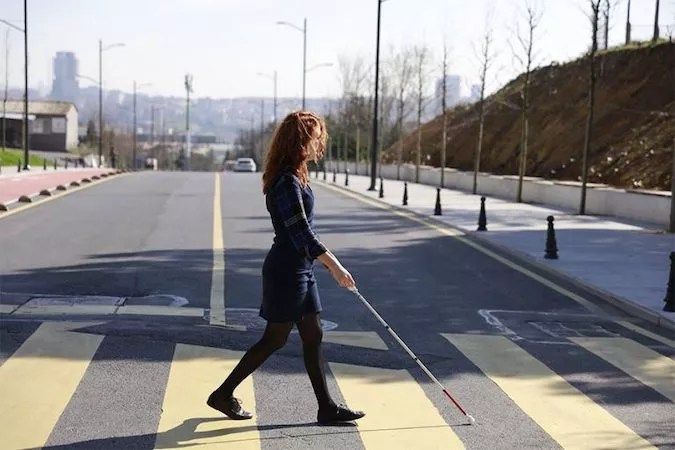 A woman is walking with WeWALK