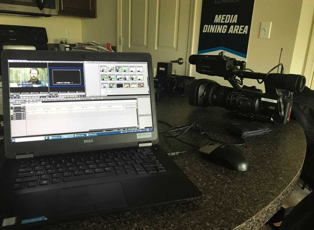 A computer and camera sit on a desk as a journalist prepares to create a video news report.