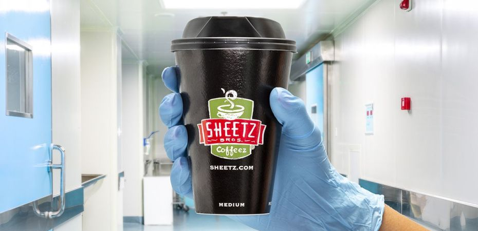 A gloved hand hold a cup of Sheetz coffee
