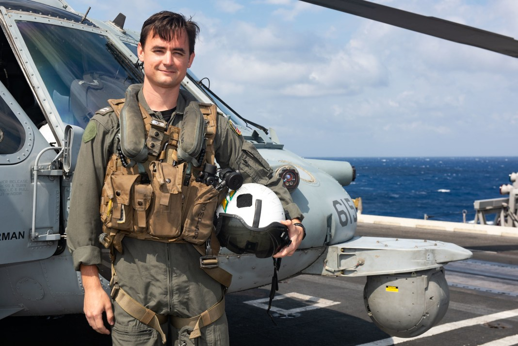 Lt. Tyler Thompson, a Navy pilot from Berryville, Virginia, poses in front of an MH-60S Sea Hawk helicopter.