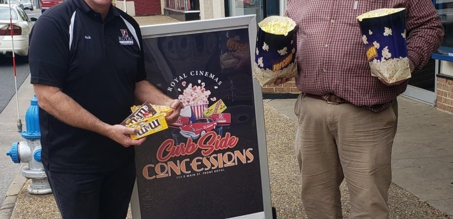 Movie theater owner Rick Novak holds M&M candy next to Wells Fargo's George Karnes who is holding to large popcorn bags.