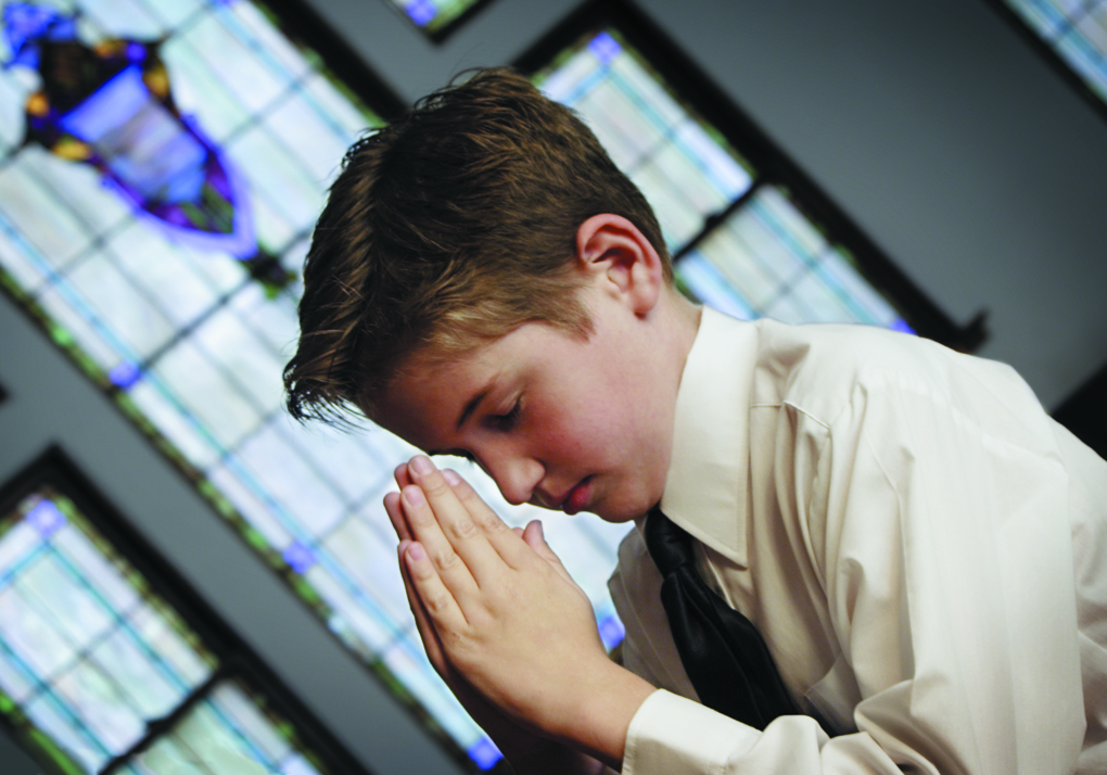 A boy prays in a church.