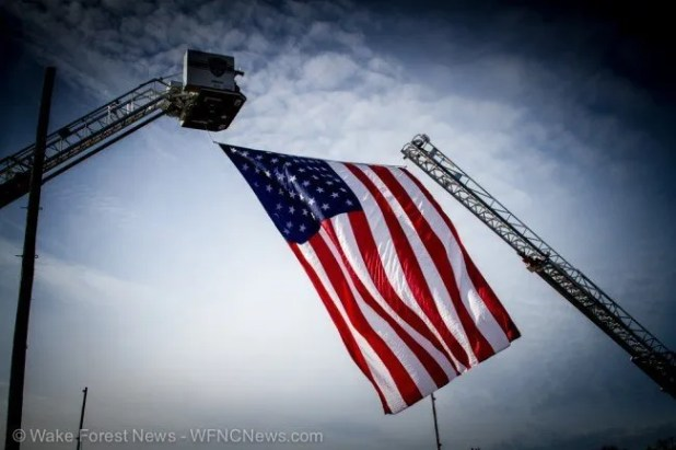 A giant flag hangs across East Main Street in Youngsville from ladder trucks from the Wake Forest Fire Department and Louisburg Fire Department.
