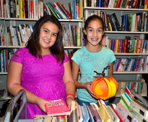 Two girls buying books at the Winters Freinds of the Library book sale room.
