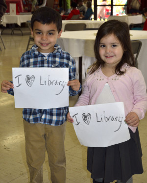 Two youngsters showing their library love at the Winters Friends of the Library Family Holiday Festival
