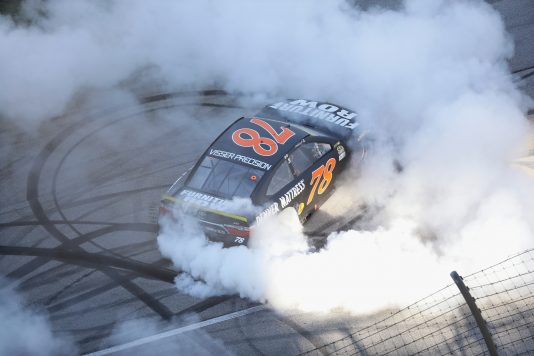 JOLIET, IL - SEPTEMBER 18:  Martin Truex Jr, driver of the #78 Furniture Row/Denver Mattress Toyota, celebrates with a burnout after winning the NASCAR Sprint Cup Series Teenage Mutant Ninja Turtles 400 at Chicagoland Speedway on September 18, 2016 in Joliet, Illinois.  (Photo by Jonathan Daniel/Getty Images)