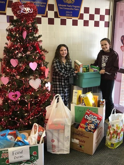Students displaying food drive items