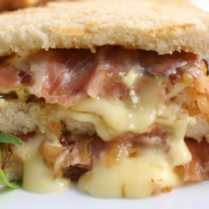 Panini sandwiches are warm and cheesy comfort food. This panini is filled with salty prosciutto, creamy brie cheese, fig jam, and caramelized onions.