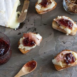 Brie with caramelized onions, prosciutto, and fig jam is an easy-to-make appetizer that works well for all occasions, from dinner parties to game day parties! | WhatAGirlEats.com