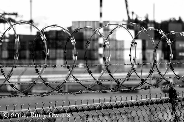This is a shot of the cargo container yard at the Port of Seattle, from behind the protective razor wire that surrounds miles of land off-limits to anyone but companies who use the port, employees, unions like Teamsters who run the unloading of goods, security teams, and those working on the ships and planes that come and go (2014).