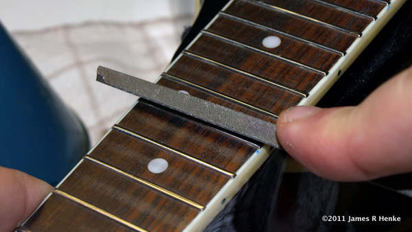 A triangle file with a rounded edge for fret side profiling.