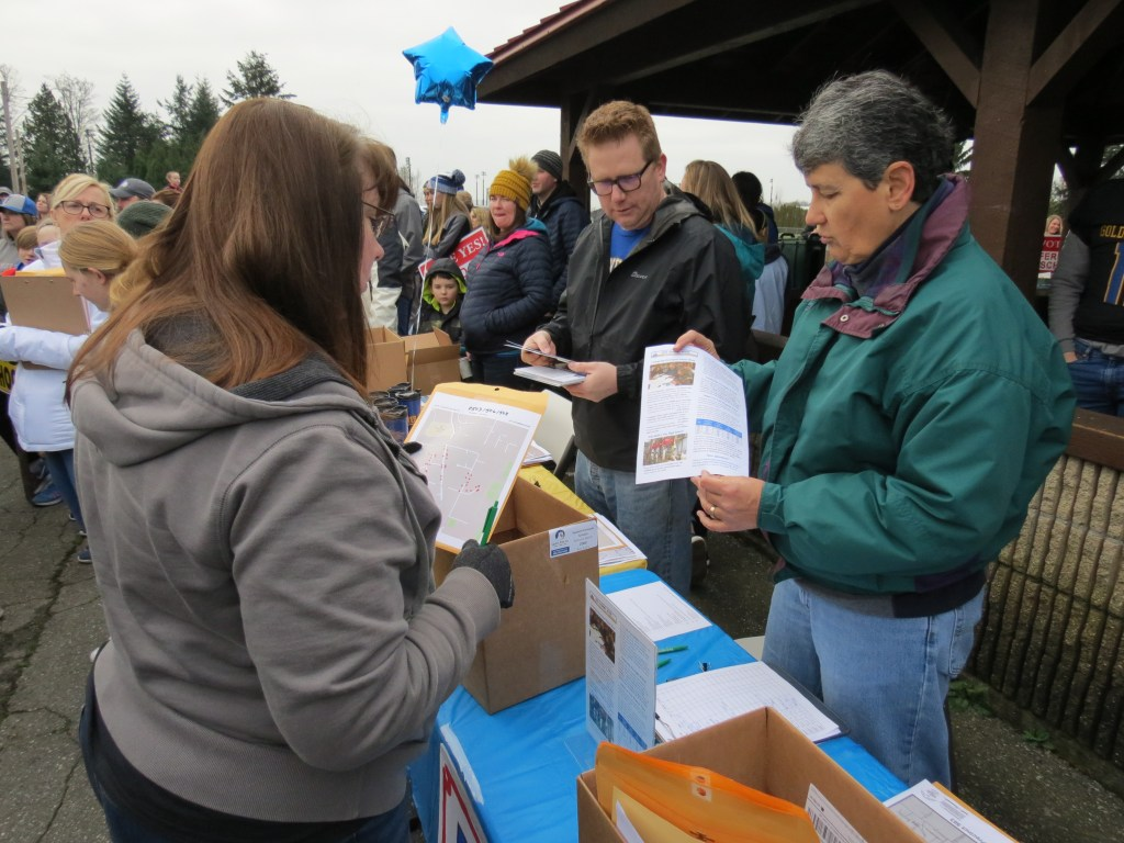 Support Ferndale Schools volunteers, Rob Fickeisen and Cathy Watson, hand out doorbelling assignments to volunteers during a School bond proposal support rally at Pioneer Park (January 26, 2019). Photo: My Ferndale News