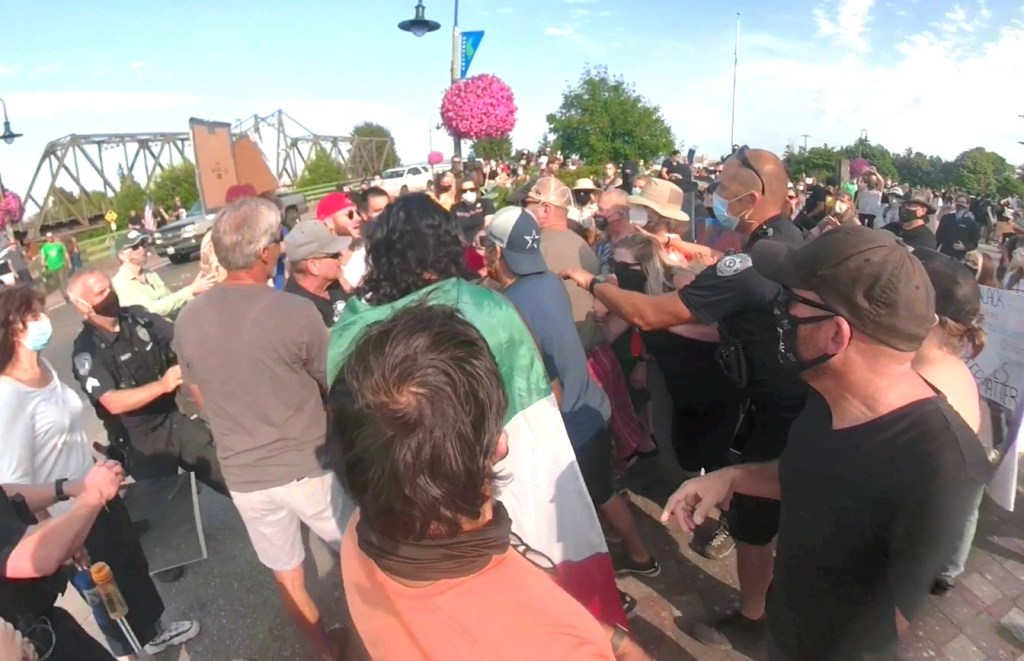 Still from a video showing Ferndale Police officers arriving to break up a scuffle during 2 rallies in downtown Ferndale (July 31, 2020).