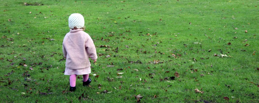 toddler walking across grass