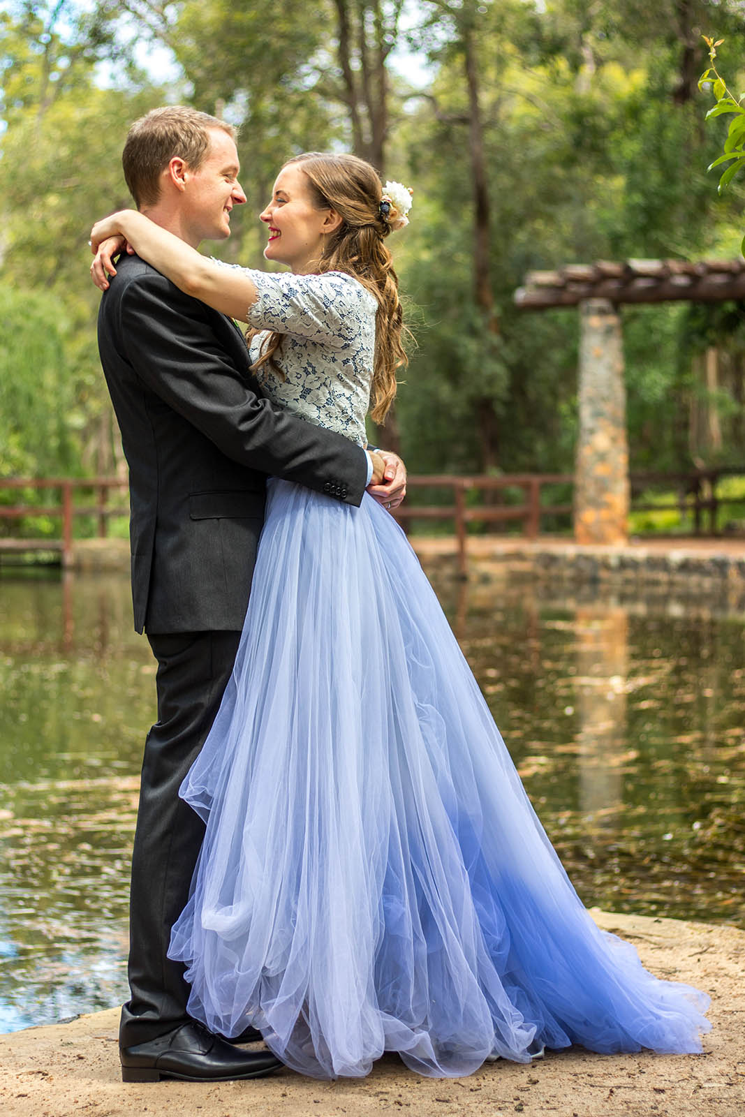 Bride and groom embracing each other poolside at Araluen Botanic Park