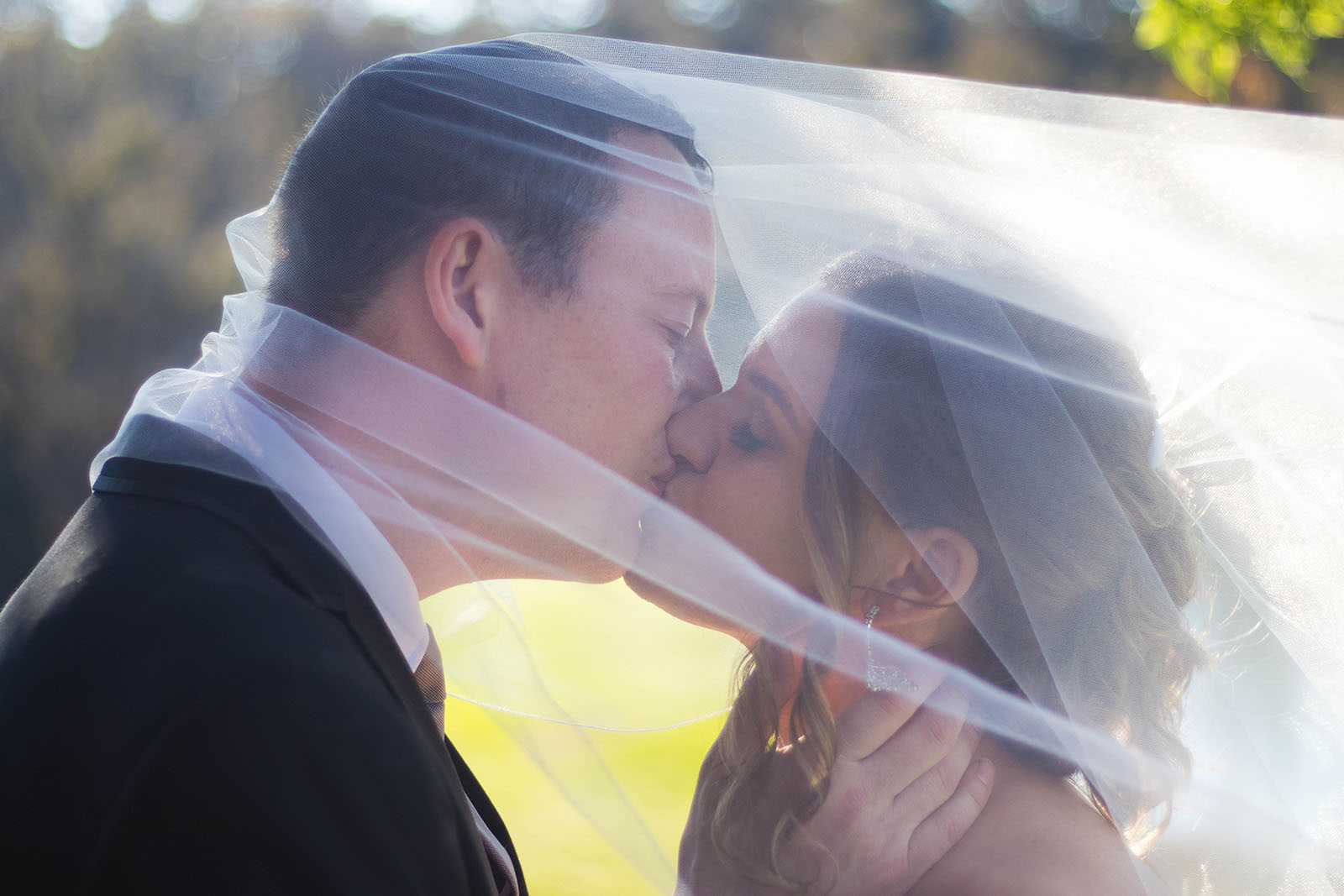 Bride and groom kissing under veil at Clover Cottage Retreat, Manjimup