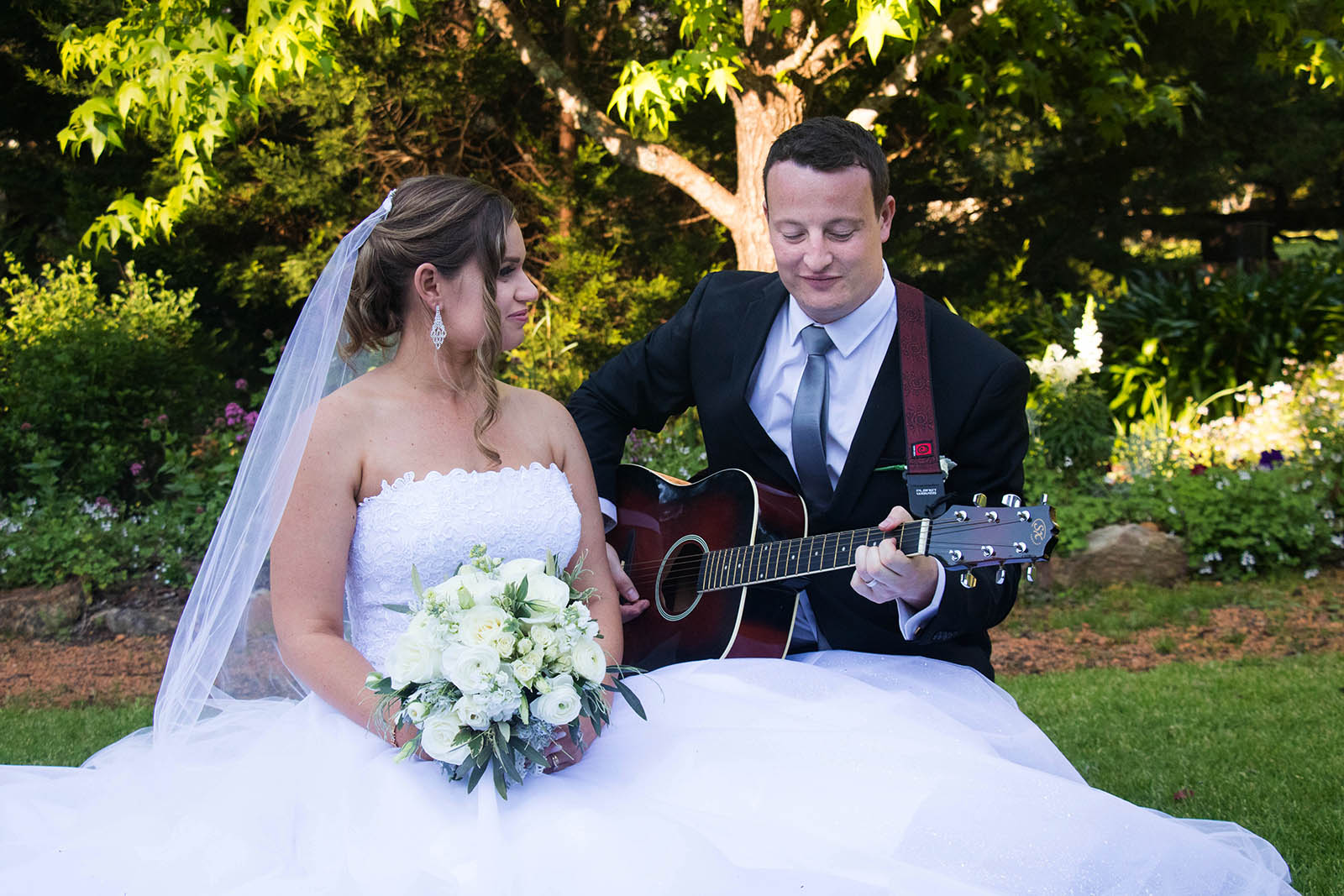 Groom plays the guitar for his bride at Clover Cottage Retreat, Manjimup