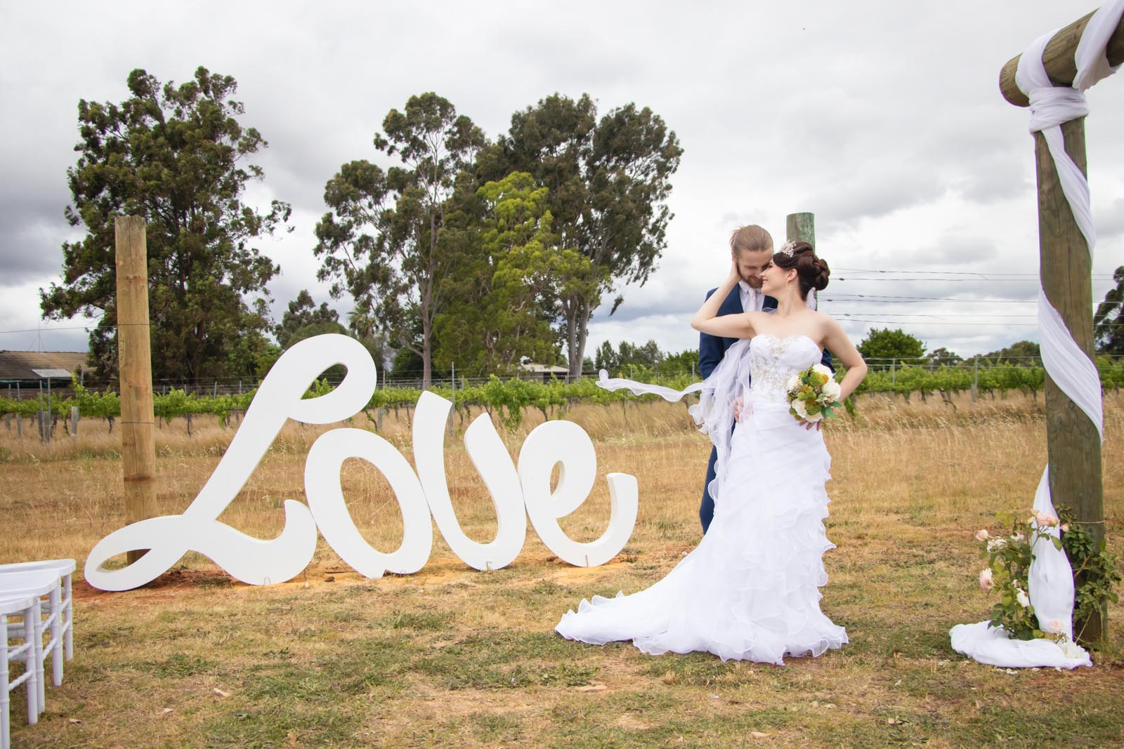 Bride and groom embracing with love sign