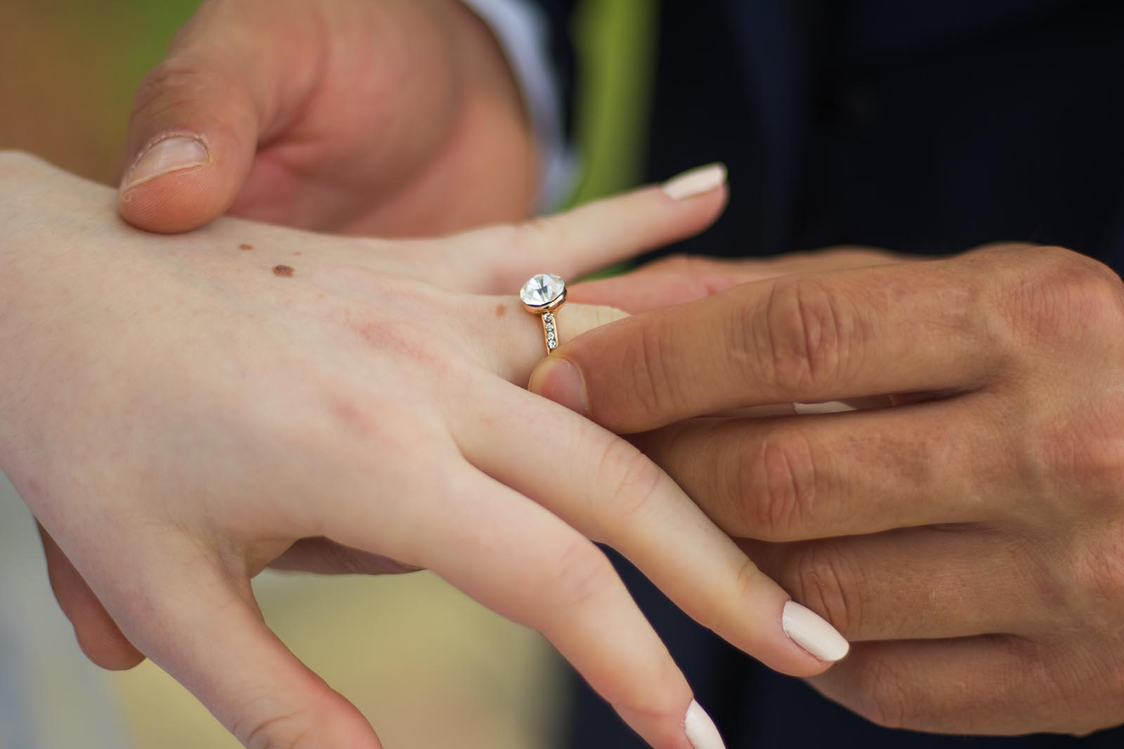 Closeup of groom placing ring on bride's finger