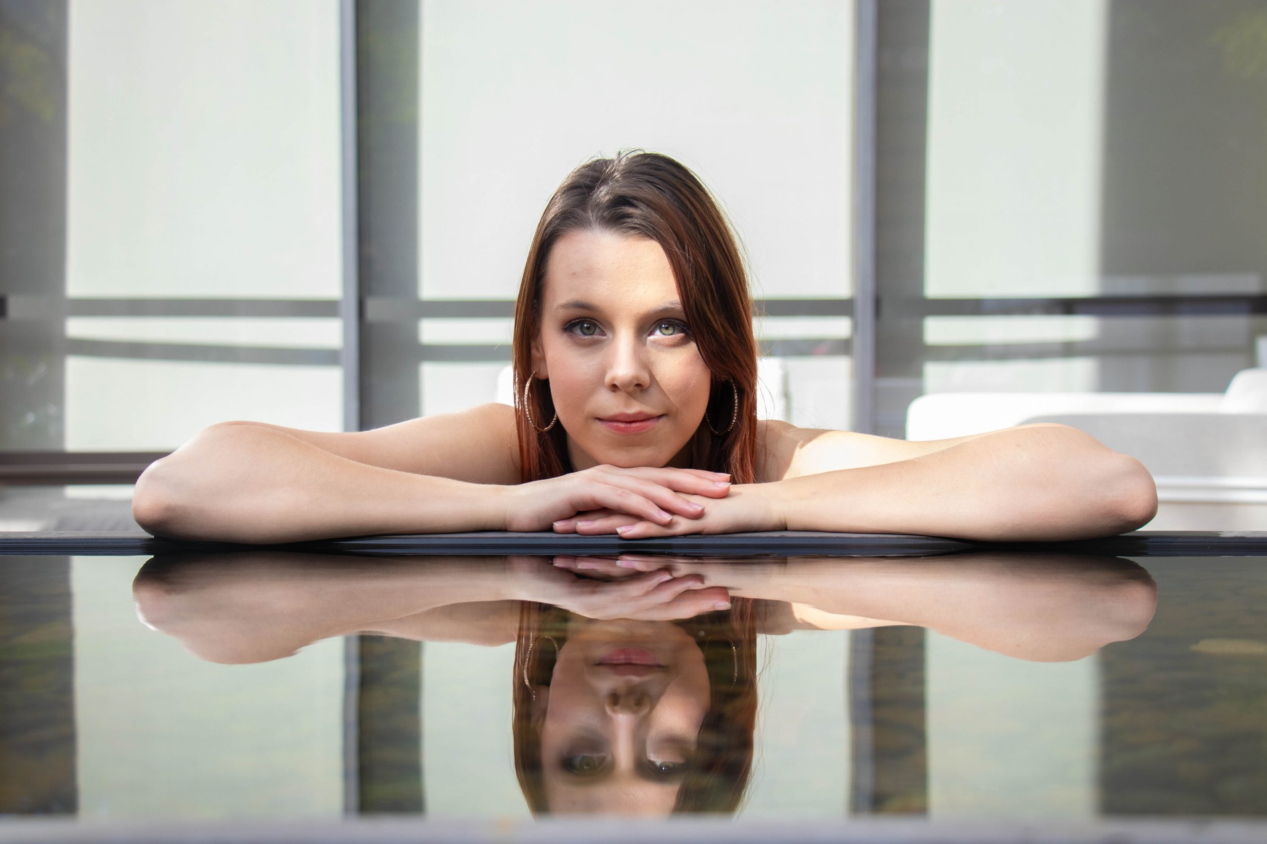 Girl deep in thought with reflective pool