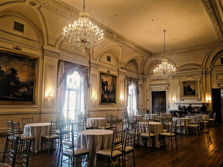 Grand ballroom with chandeliers, paintings, and tables at Oheka Castle on Long Island