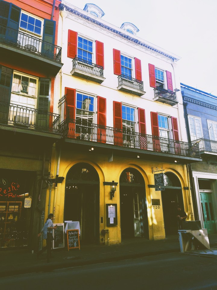 A yellow two story building with red shutters showing the famous architecture of New Orleans