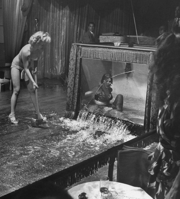 Evangelina smashes a water tank with performer inside. She stands on stage in bikini and heels holding a hammer. Water pours from tank and girl inside of tank appears to be in shock.