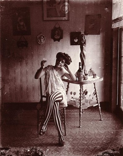 Storyville prostitute in black and shite striped stockings and black heels with messy bun sits and has a drink on a chair.