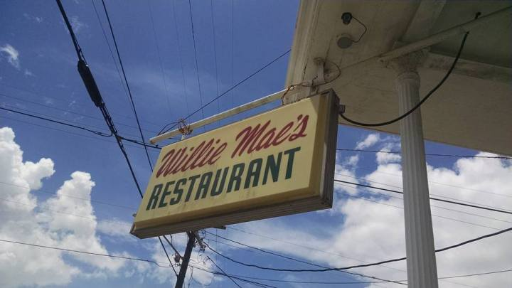 The sign for Willie Mae's Restaurant set against a blue and cloudy sky.