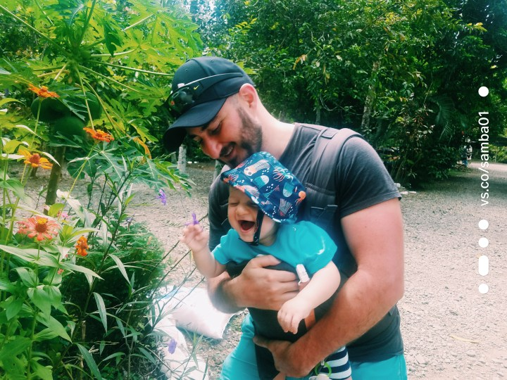A father holds his baby who is laughing as he smells a bunch of flowers