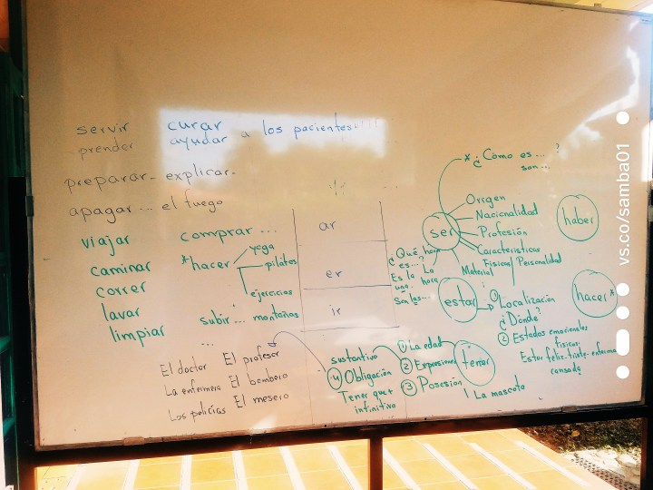 A white board is full of Spanish verbs and how to conjugate them.