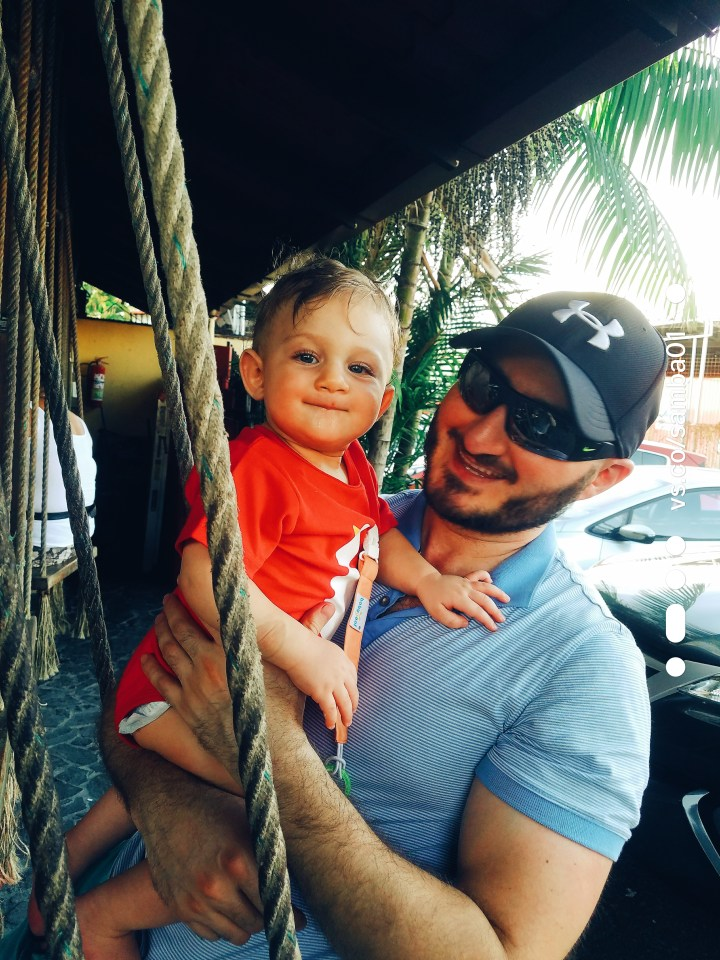 Father and son sit on a swing at a taco lunch spot in Jaco, Costa Rica.