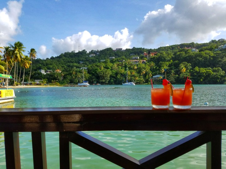 Two glasses of red rum punch in front of Marigot Bay, St Lucia. These are the perfect drinks to have during a trip to St Lucia with a friend