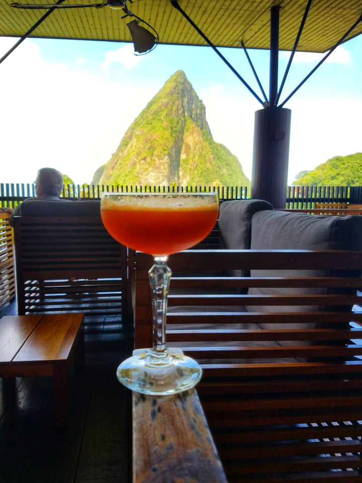 A view of St Lucia's pitons from Boucan restaurant by Hotel Chocolat. There is a fruity cocktail positioned in front of the Pitons view. You must see this view even if you only have one day in Soufriere.