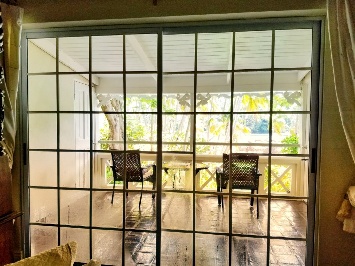 A beautiful deck attached to a hotel room through a sliding glass door. It's the perfect place to sit and listen to music during a trip to St Lucia with a friend