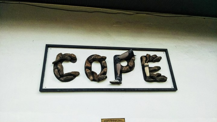 """A sign reading """"COPE"""" made of prosthetic welcomes visitors to the COPE center."""