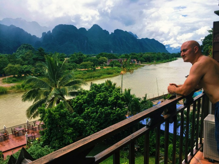 A shirtless bald man looking out over a river with mountains and palm trees in the background in Laos