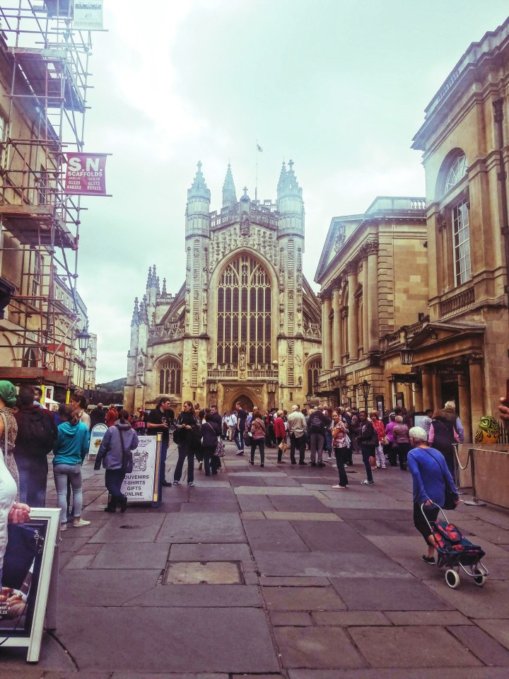 A long shot of Bath Cathedral in Bath, England. There are people gathered on the street.