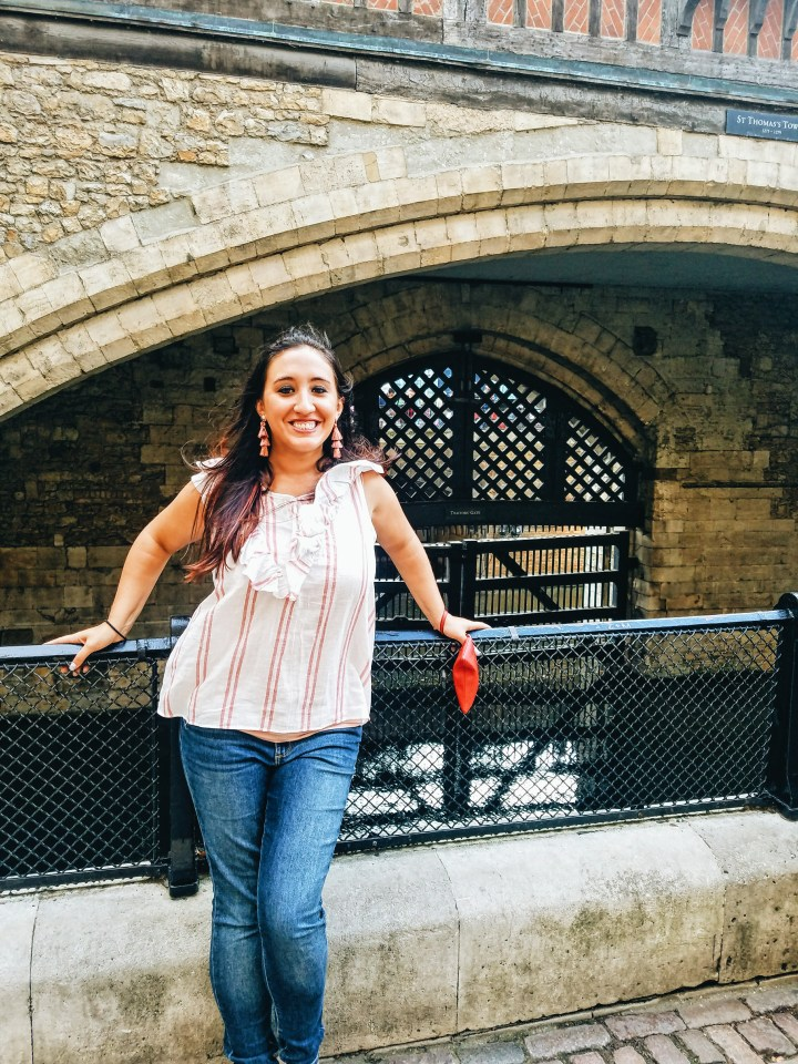 A woman in a white and pink striped shirt and jeans stands in front of Traitor's Gate at the tower of London