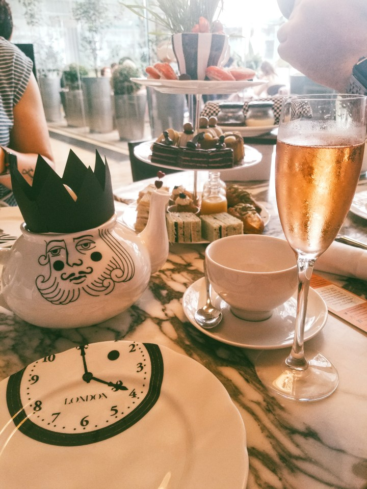 A glass of rose champagne accompanies tea and treats at the Sanderson hotel's Mad Hatter Afternoon Tea in London
