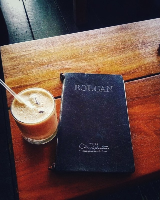 "Picture of black leather menu with words ""Boucan"" and ""Hotel Chocolate"" at bottom. Chocolate drink with straw in clear glass next to it. The best place to eat if you have limited time, like one day in Soufriere."