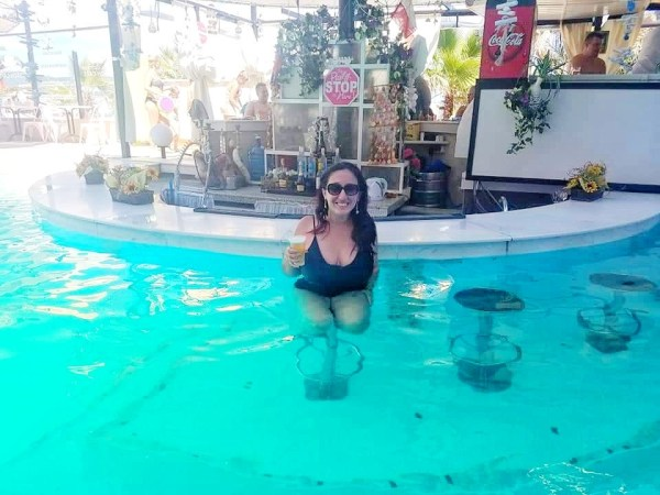 A woman is sitting in a pool holding a beer, hiding from a weird couple in Bulgaria.