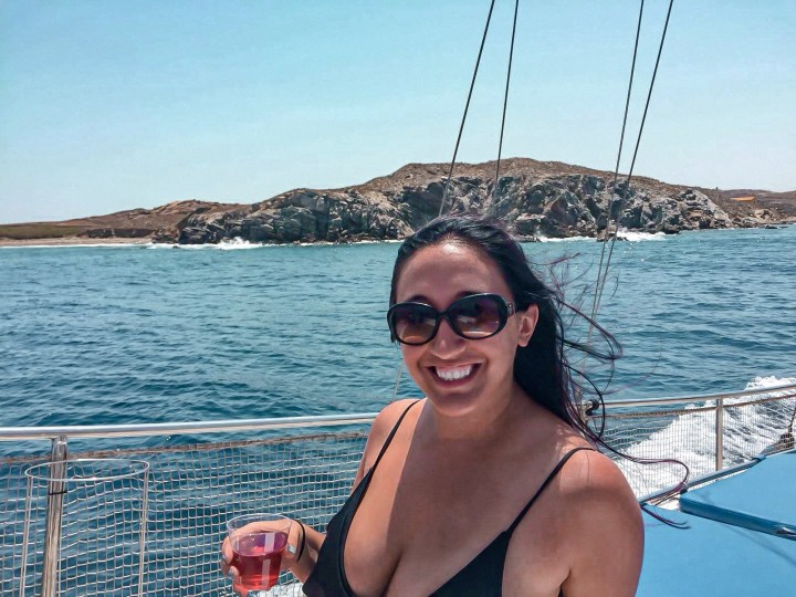 A woman holds a plastic glass full of rose, is drunk and sailing around Mykonos and smiles at the camera wearing sunglasses.