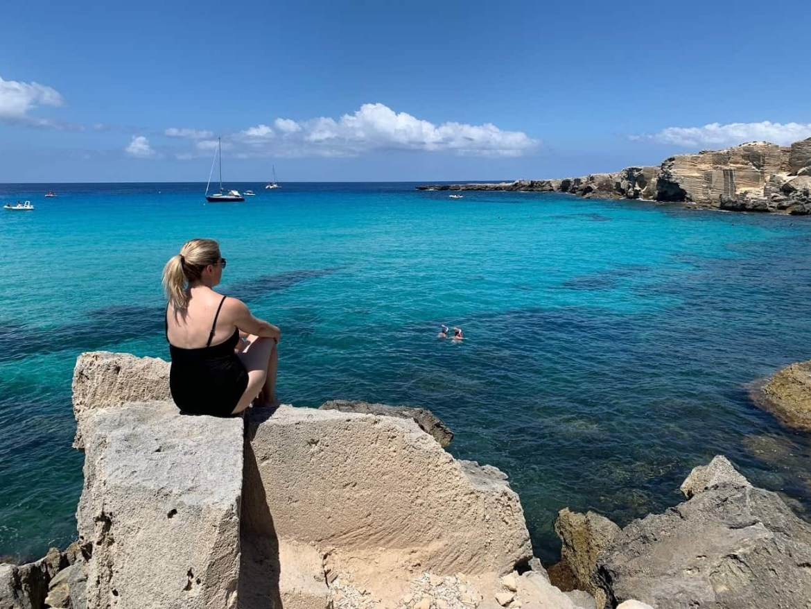 Sitting on a rock gazing at the blue waters of Cala Rossa