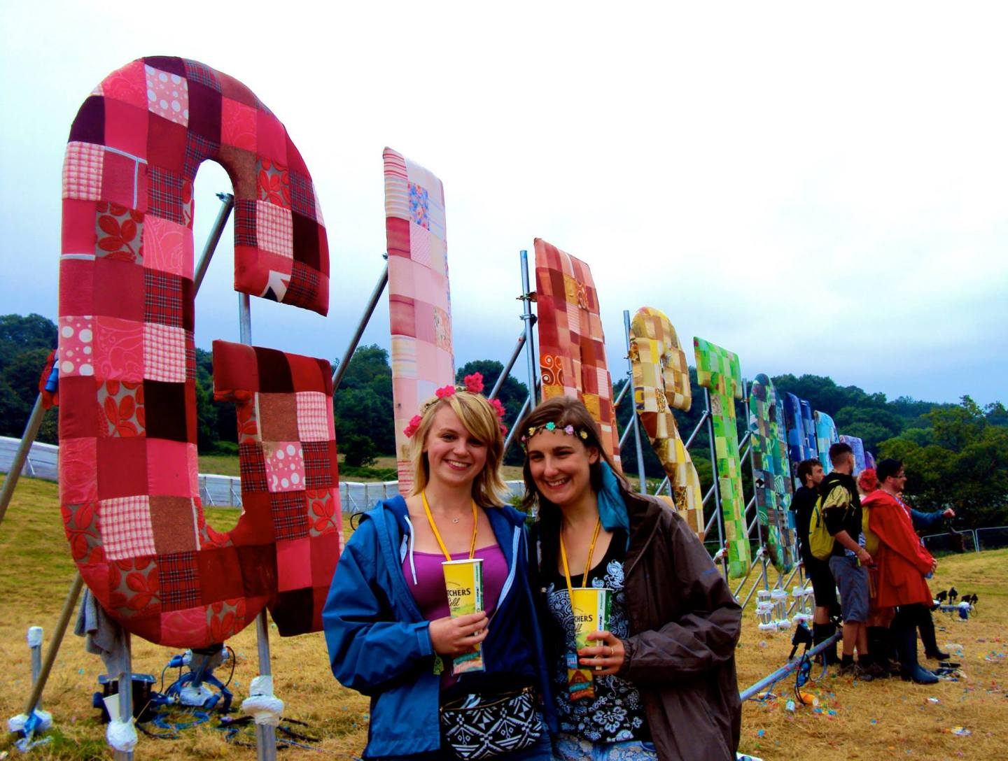 Girls in front of the Glastonbury sign