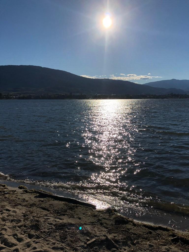 Sun over the beach next to Lake Osoyoos