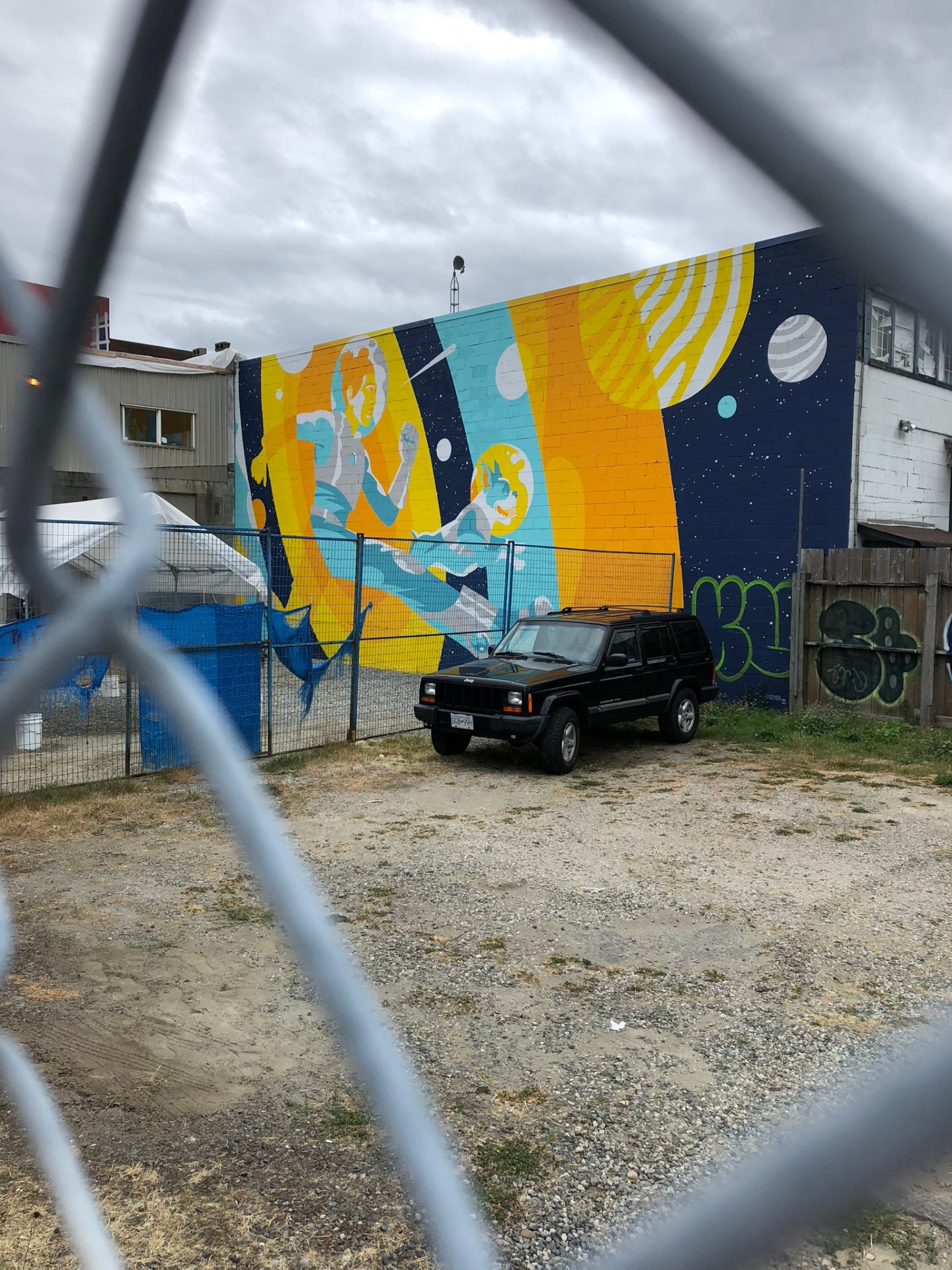 Colourful mural through a fence at the Vancouver Mural Festival